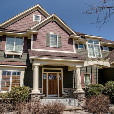 Home with stone siding brown roof and white trim