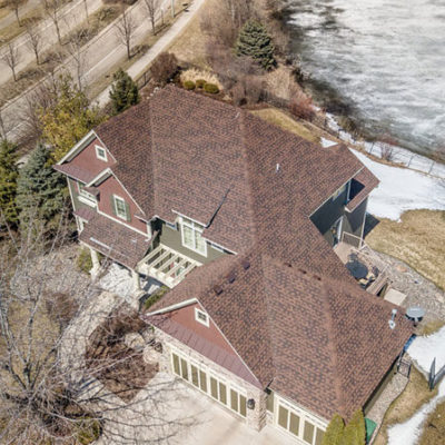 Drone view of home with brown and black colored roof